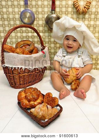 A sitting boy baby dressed as a baker