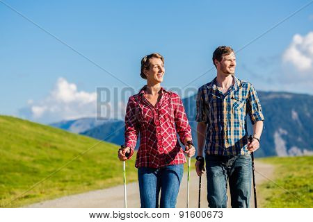 Couple doing Nordic walking exercise in mountains with alpine panorama