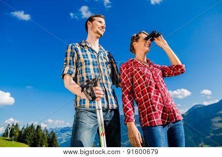 Couple enjoying view hiking in the alpine mountains looking thru binoculars
