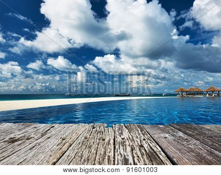 Swimming pool and old wooden pier in the tropical hotel