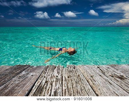 Woman in bikini lying on water at tropical beach