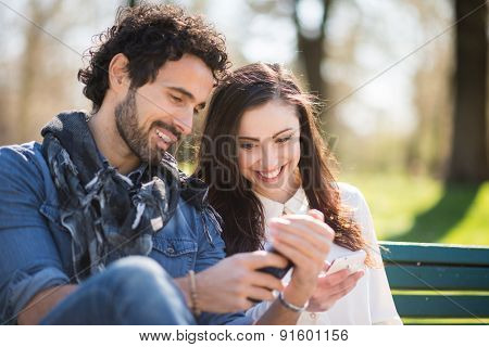 Smiling man showing his mobile phone to a girl