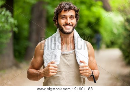 Young man training himself outdoor and smiling at camera