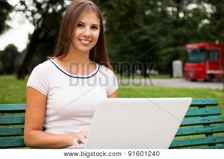 Young woman using a laptop computer in a park