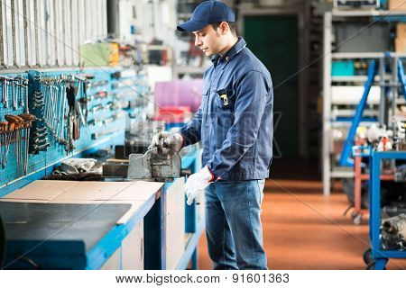 Worker securing a metal plate in a vise