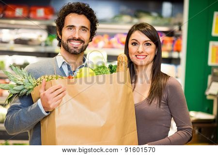 Smiling couple holding a shopping bag full of food in a supermarket