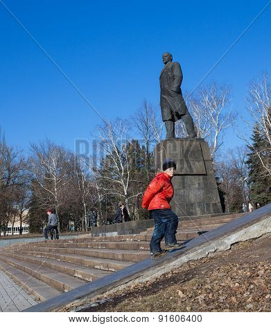 Makeevka, Ukraine - February, 22, 2015: The Boy On The Background Of The Monument To Vladimir Lenin