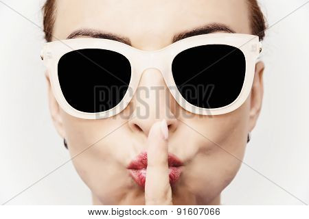 Young Caucasian Glamour Woman With Stylish Sun glasses And Finger To Her Mouth