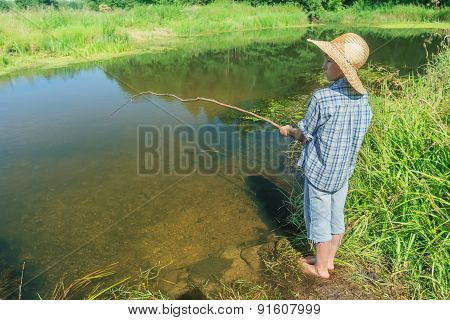 Barefoot fishing boy angling in transparent brownish water body