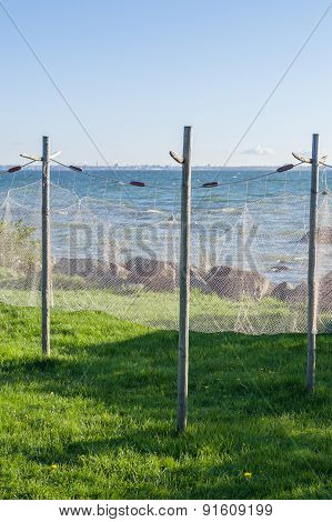 Old Style Fishing Net Hanging To Dry Near Seashore