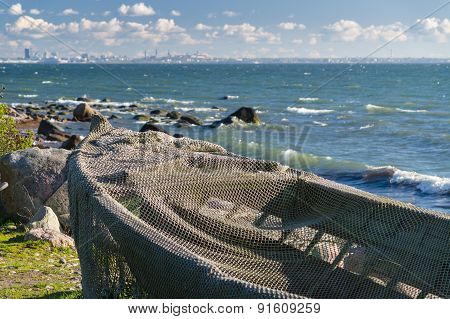 Boat Covered By Fisherman Net At Seashore And Modern Cityscape On Background