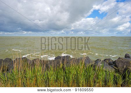 Deteriorating weather over a dike along a sea in spring