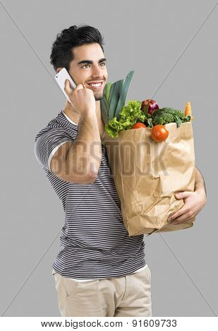 Handsome young man carrying a bag full of vegetables and making a phone call, isolated over gray background