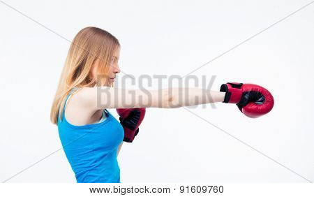 Side view portrait of a young woman training in boxing gloves isolated on a white background. Looking away