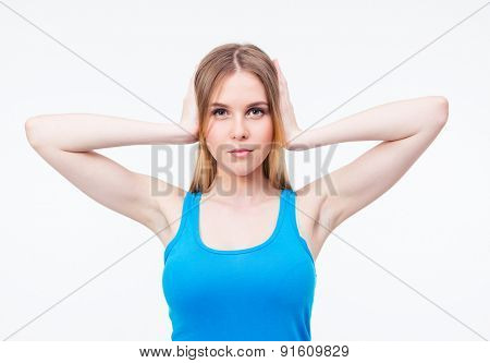 Casual young cute woman covering her ears isolated on a white background. Looking at camera