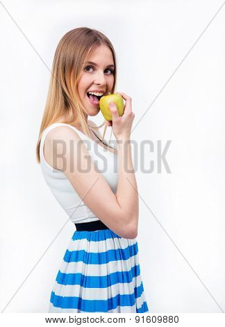 Happy young woman eating green apple over gray background. Looking at camera