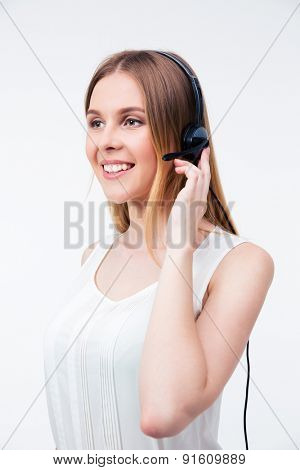 Happy young female operator in headset over gray background. Looking away
