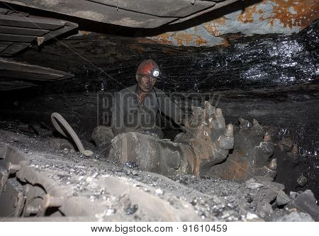 Donetsk, Ukraine - August, 16, 2013: Miner Near The Coal Mining Shearer. Mine Is Named Chelyuskintse