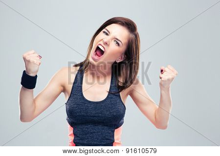Angry young sports woman shouting on gray background and looking at camera