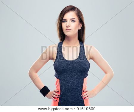 Pretty sportive woman standing on gray background. Looking at camera