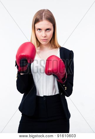 Portrait of a businesswoman in boxing gloves looking at camera over gray background