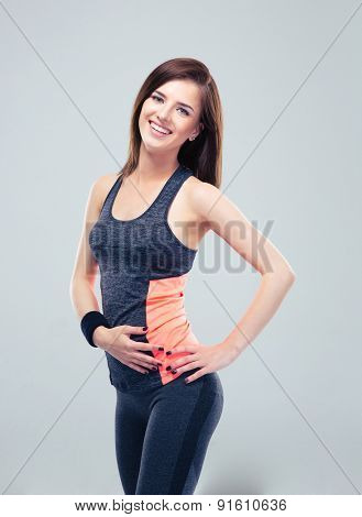 Cheerful fitness woman posing over gray background and looking at camera