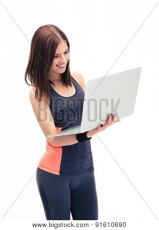 Smiling fitness woman using laptop isolated on a white background