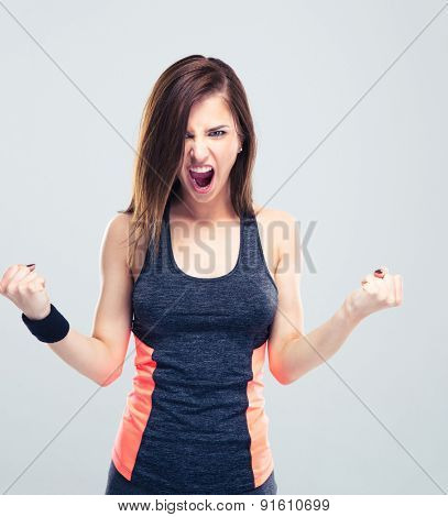 Angry young fitness woman screaming on gray background and looking at camera