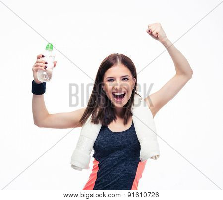 Fitness woman with towel and bottle of water celebrating her victory isolated on a white background. Looking at camera