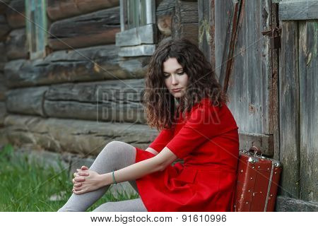 Portrait of young woman sitting in front of old log house with vintage suitcase