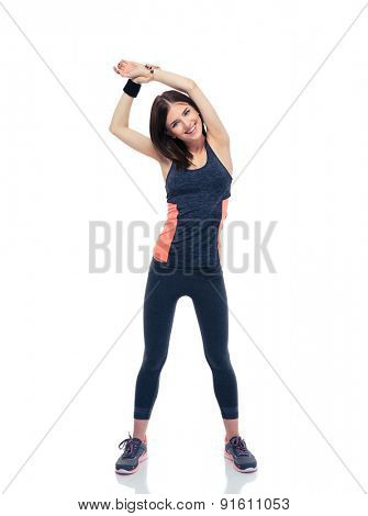 Full length portrait of a smiling sporty woman doing stretching exercise isolated on a white background. Looking at camera