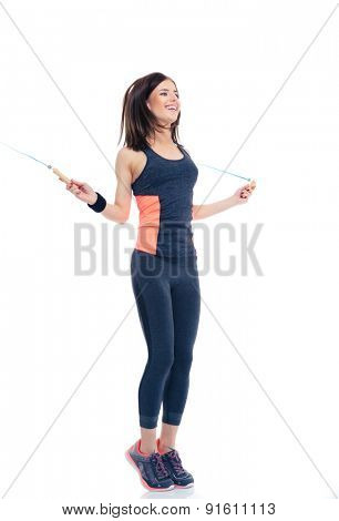 Full length portrait of a smiling woman doing exercises with jumping rope isolated on a white background