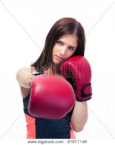 Pretty woman punching in camera with boxing glove isolated on a white background. Looking at camera