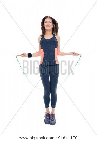 Full length portrait of a happy woman doing exercises with jumping rope isolated on a white background. Looking at camera