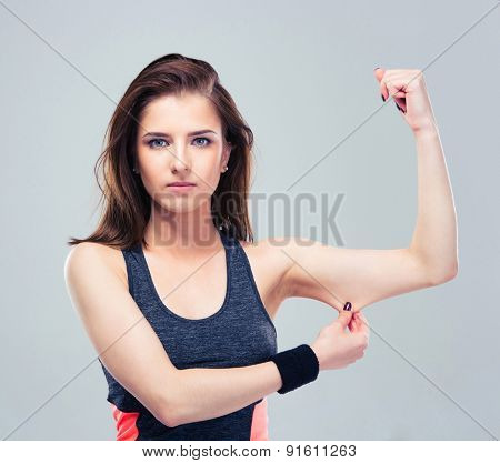 Fitness woman pinch a fat on her biceps over gray background