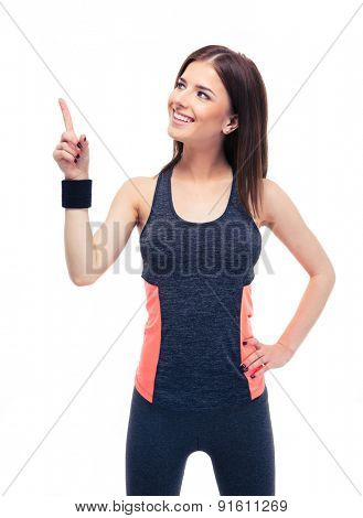 Happy beautiful fitness woman in sportswear pointing up at copyspace. Isolated on a white background