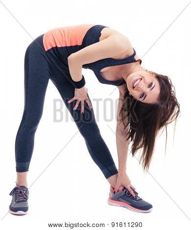 Smiling fitness woman doing stretching exercise isolated on a white background. Looking at camera