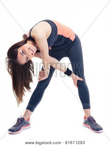 Happy fitness woman doing stretching exercise isolated on a white background. Looking at camera