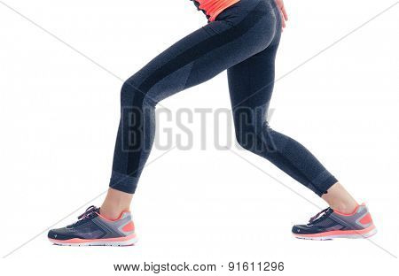 Closeup image of female fitness legs in sports wear isolated on a white background