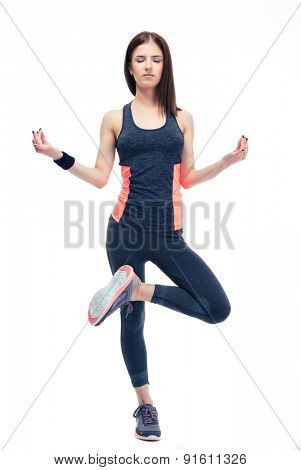 Full length portrait of a cute sports woman standing and meditating isolated on a white background