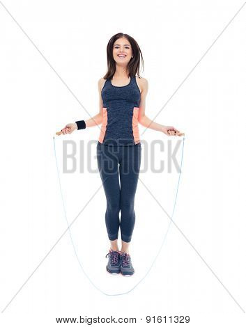 Full length portrait of a smiling fitness woman jumping with skipping rope isolated on a white background