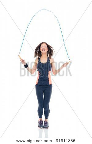 Full length portrait of a cheerful woman doing exercises with jumping rope isolated on a white background. Looking at camera