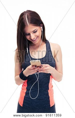 Smiling sporty woman in headphones using smartphone isolated on a white background