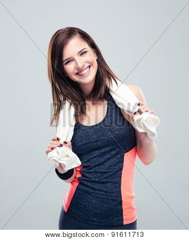 Portrait of a happy fitness woman with towel standing over gray background and looking at camera