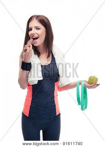 Sports woman holding apple and eating chocolate isolated on a white background and looking at camera