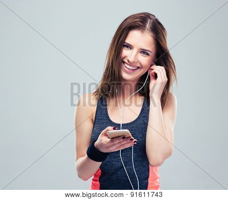 Happy sports woman with smartphone over gray background. Listening music in headphones