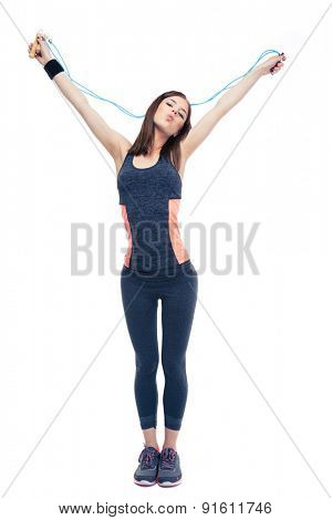 Beautiful fitness woman standing with skipping rope isolated on a white background. Looking at camera