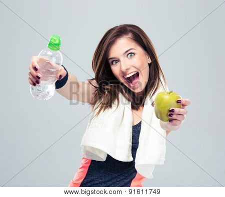 Funny sporty woman holding apple and bottle with water over gray background and looking at camera