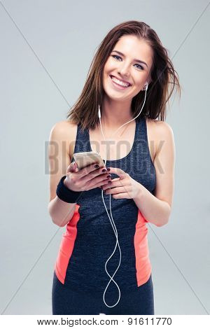Smiling fitness woman with smartphone over gray background. Listening music in headphones