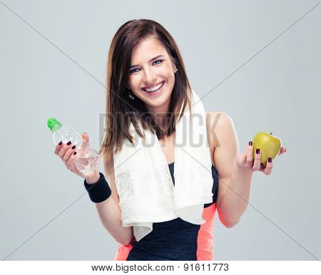 Smiling sporty woman holding apple and bottle with water over gray background. Looking at camera